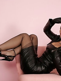 Nadja dressed in leather catsuit, stockings and high heel..