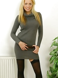 Amazing blonde in a grey jersey dress, stockings and boots.